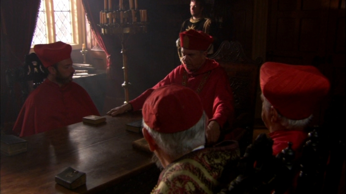 Wolsey (Sam Neill) e os altos membros da Igreja Católica em Inglaterra decidem sobre a validade do casamento real.