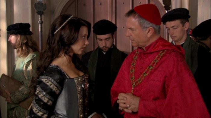"""Wolsey (Sam Neill) chama Ana Bolena (Natalie Dormer) de """"garota tola"""", mal sabendo que ela será a arma de sua queda."""