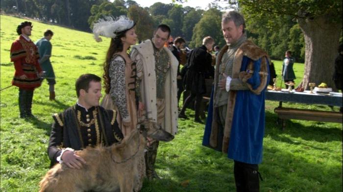 """Cena em que Ana Bolena (Natalie Dormer) presenteia o embaixador francês com um cão chamado """"Wolsey""""."""