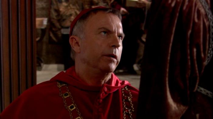 Um desesperador Cardeal Wolsey (Sam Neill) se ajoelha perante Catarina de Aragão, implorando que esta aceite a vontade do rei.
