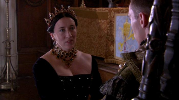 Catarina de Aragão (Maria Doyle Kennedy) se defende perante o rei, durante o julgamento.