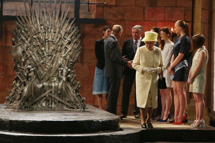 A Rainha Elizabeth II ao lado do Trono de Ferro, enquanto o príncipe Philip conversa com o elenco da série.