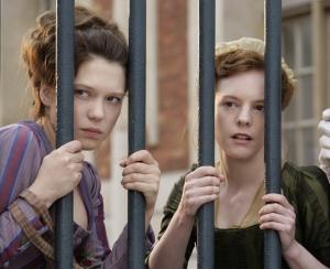 Sidonie ao lado de sua amiga, Honirine (Julie-Marie Parmentier) espiam a vida da nobreza palaciana.