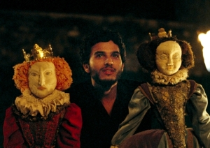 David Rizzio (Mehdi Dehbi) e seu teatro de fantoches, com as bonecas de Elizabeth I e Maria Stuart.