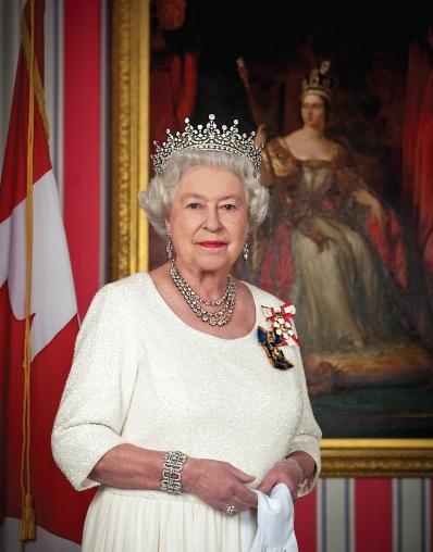 Rainha Elizabeth II tendo ao fundo o retrato de sua antecessora, a rainha Vitória.