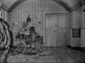 Quarto onde os Romanov foram assassinados. Essa fotografia foi tirada momentos depois da execução. Perceba os estragos na parede feitos pelos tiros.