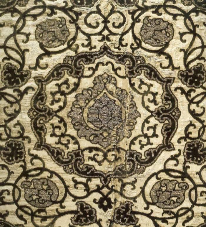 Detalhe da estampa do vestido que Eleonora de Toledo usa no seu retrato. O tecido,jjá bastante desgastado pelo tempo, é adornado por arabescos de veludo preto sobre cetim branco. O brocado de ouro foi parcialmente removido.
